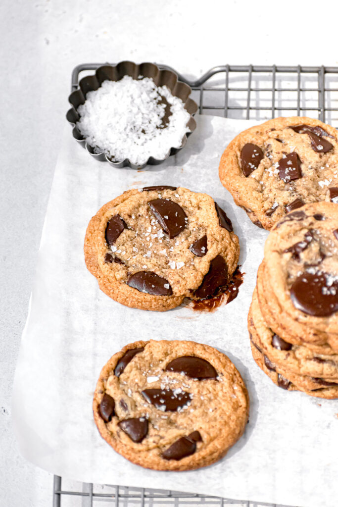 cookies on parchment lined wire rack with bowl of flaky sea salt