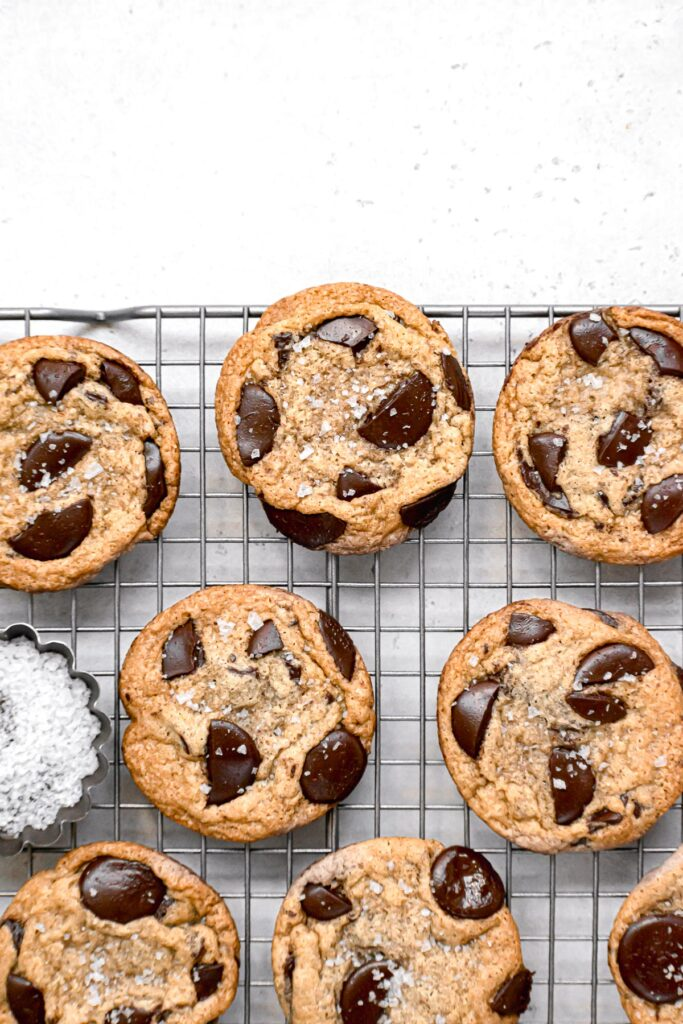 chocolate chip cookies on wire rack with bowl of flaky sea salt