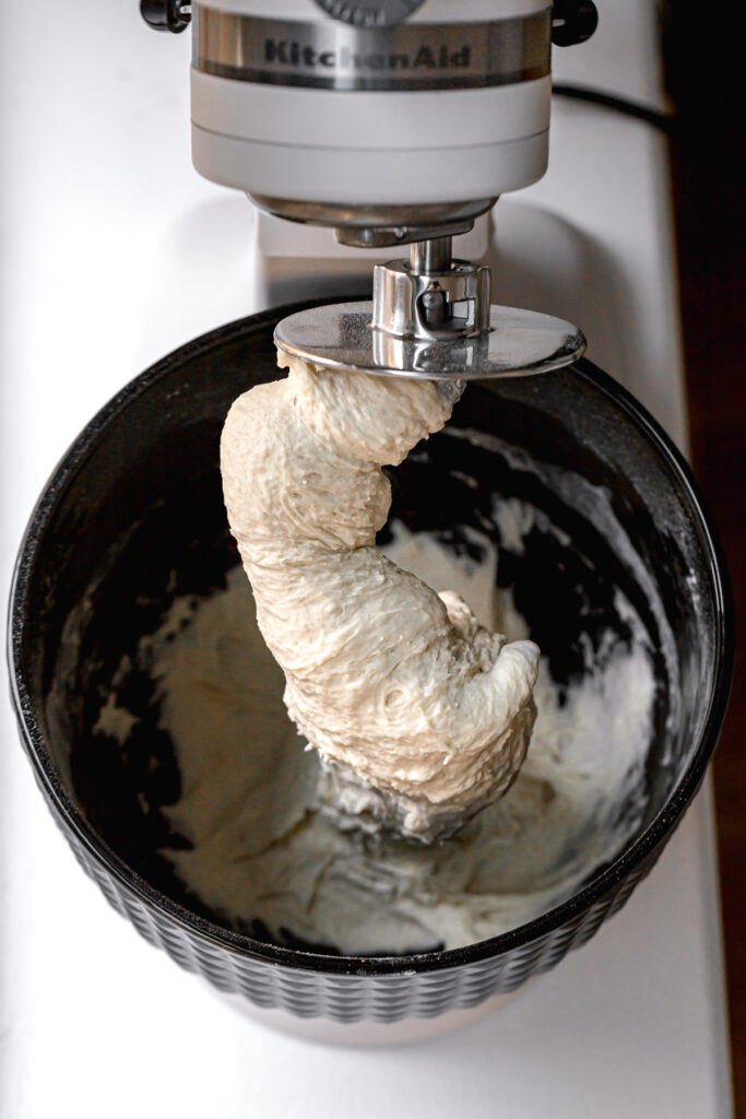 bagel dough wrapped around dough hook in stand mixer