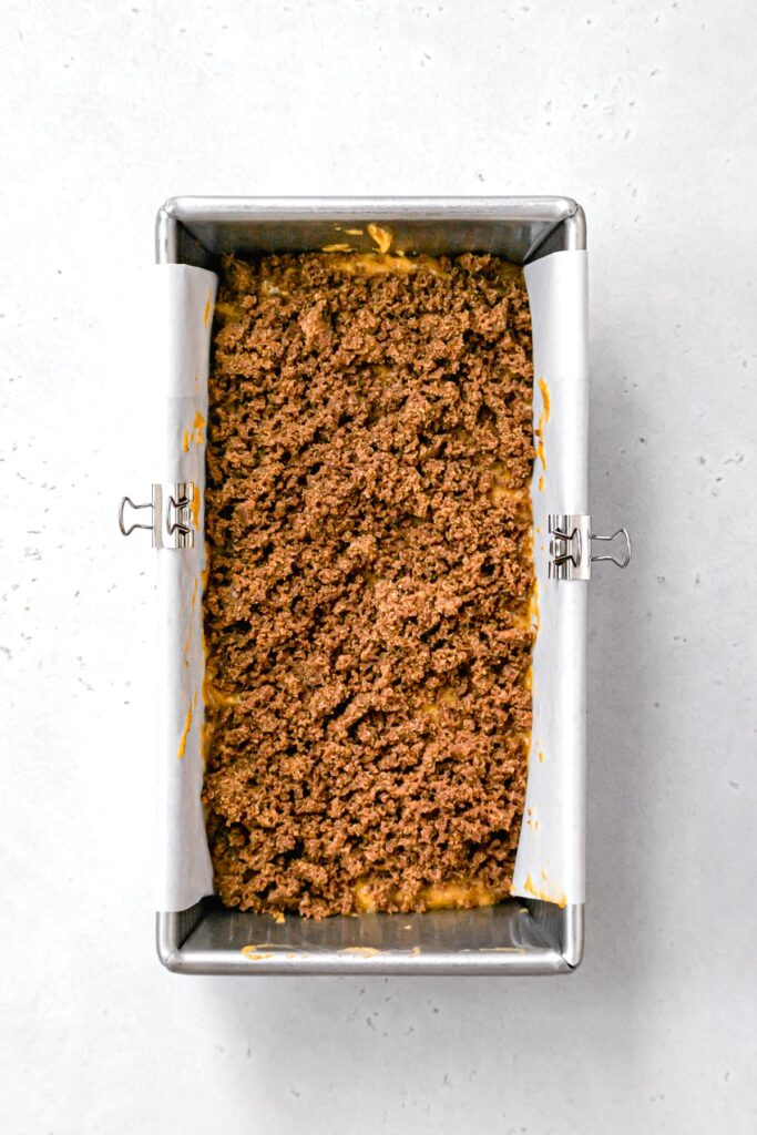 cinnamon swirl mixture on top of first layer of pumpkin bread batter in loaf pan