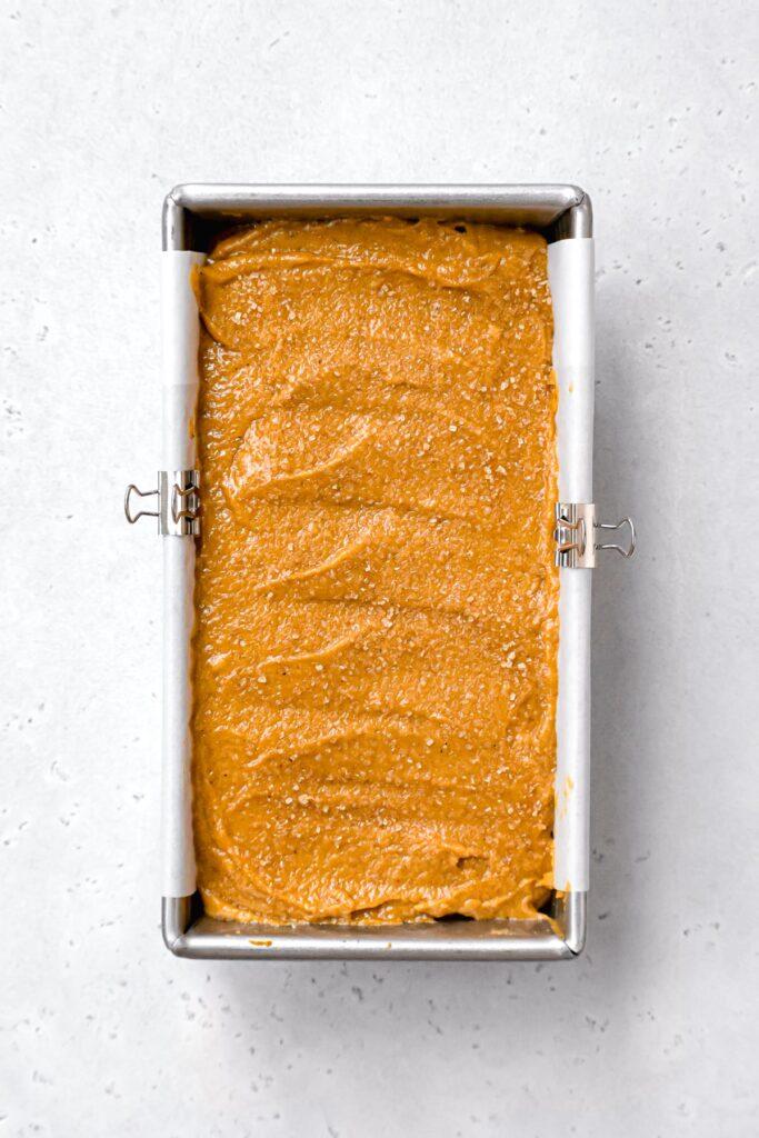 pumpkin bread batter with turbinado sugar on top in metal loaf pan