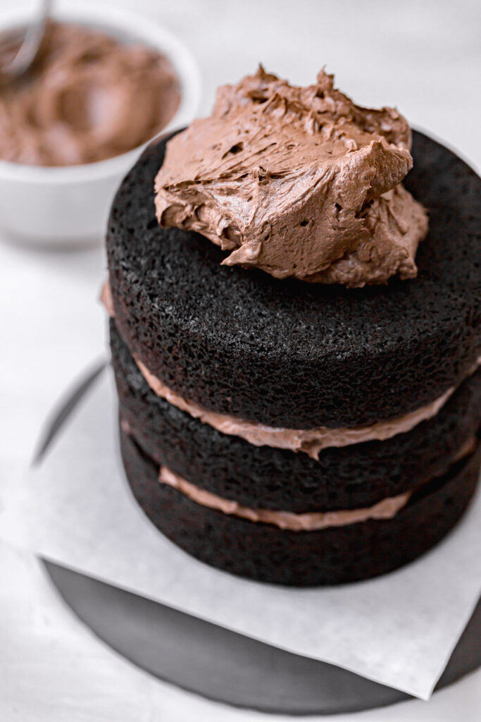 large dollop of black cocoa frosting on top of layered cake