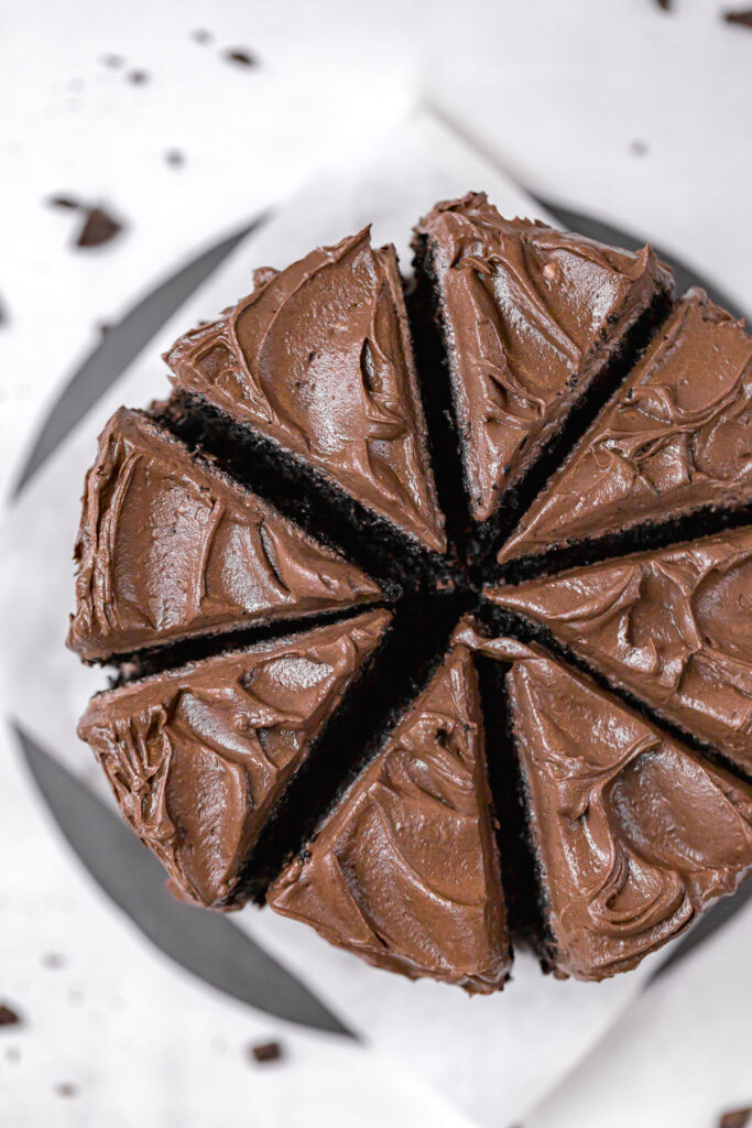 above angle of black cocoa cake sliced into 8 pieces