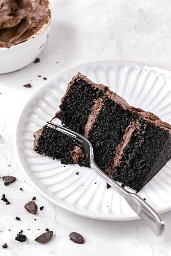 slice of black velvet cake on white plate with fork