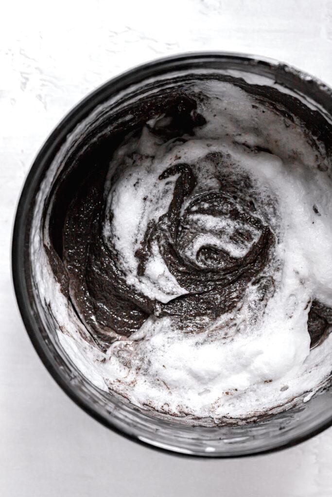 whipped egg whites being folded into black velvet cake batter