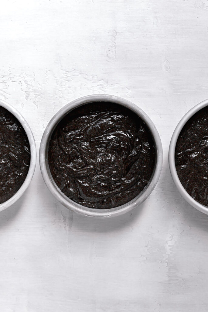black cocoa cake batter in 6 inch cake pans